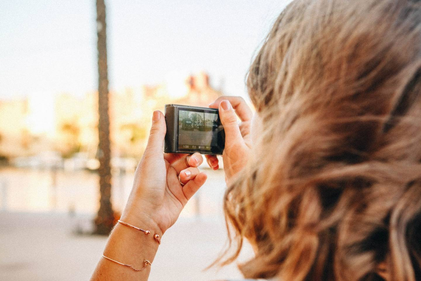 A woman takes a photo with a digital point-and-shoot