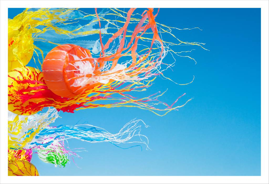 Colorful jellyfish kites made of plastic blow through the air.