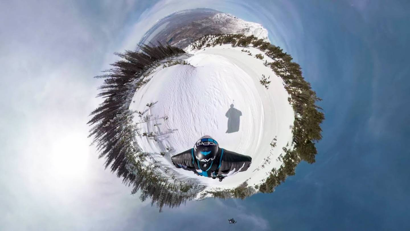 Photo in little planet of Marshall Miller in full wingsuit descent over snow-capped mountains
