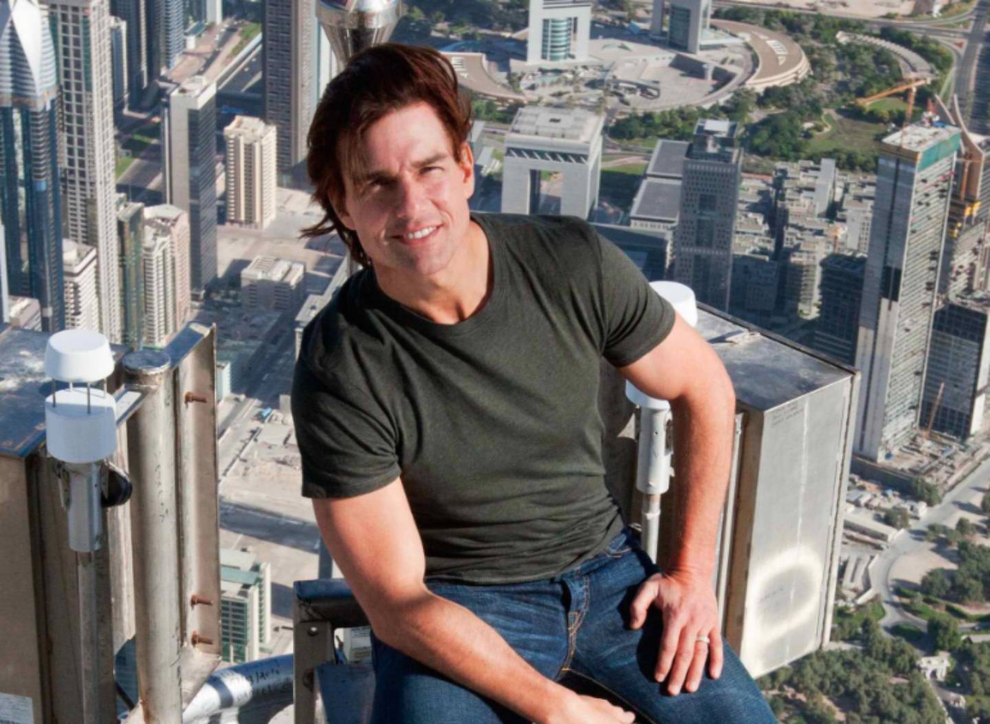 Photo de Tom Cruise en train de sourire, assis devant une ville pleine de buildings