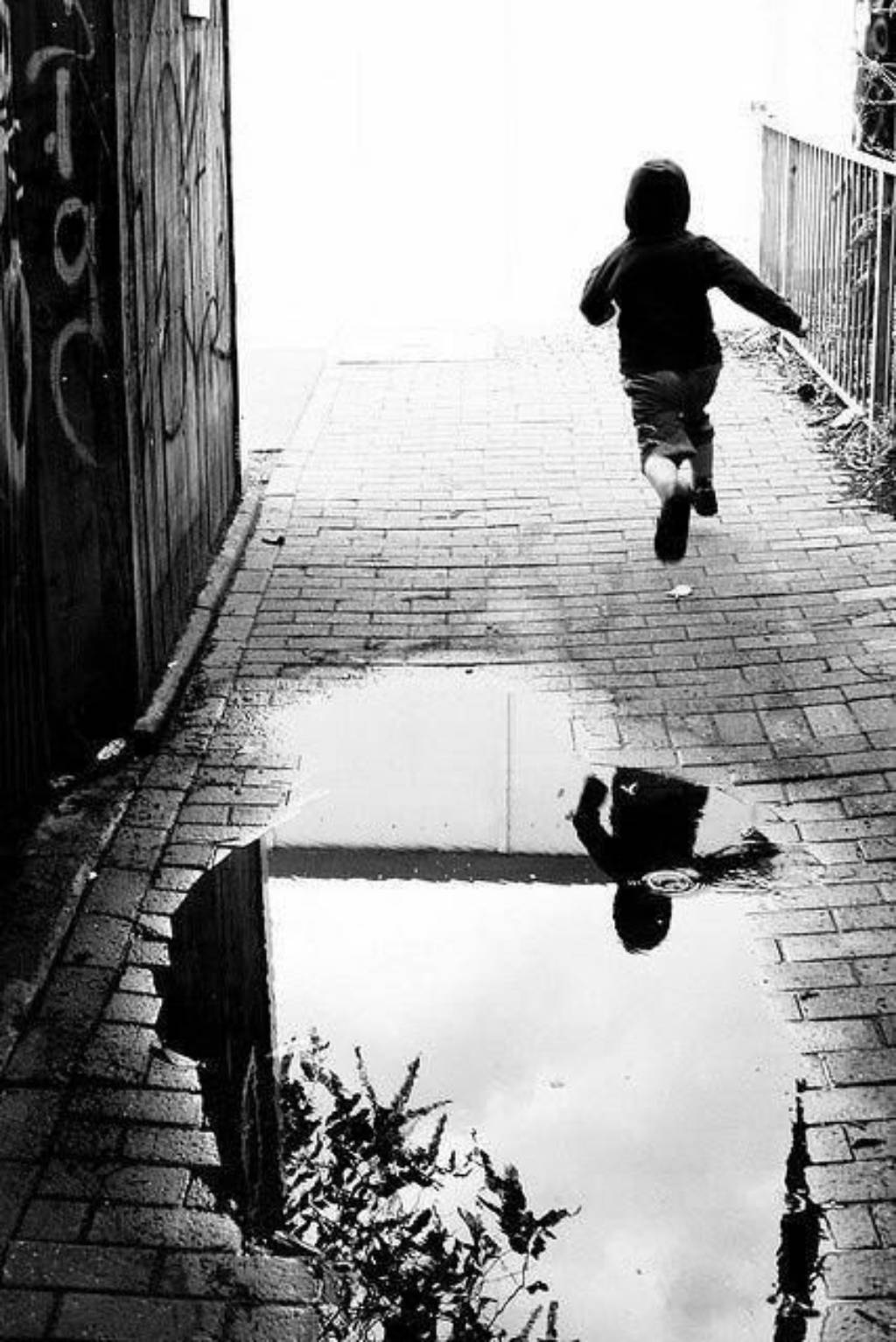 Kid jumping puddle by Henri Cartier Bresson