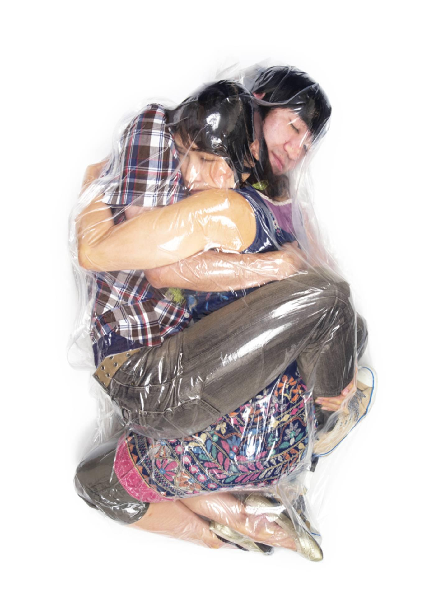 Photo of a couple in vacuumed plastic bag