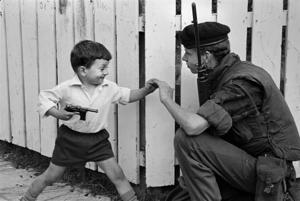 Philip Jones Griffiths - Un enfant s'amusant avec un soldat armé